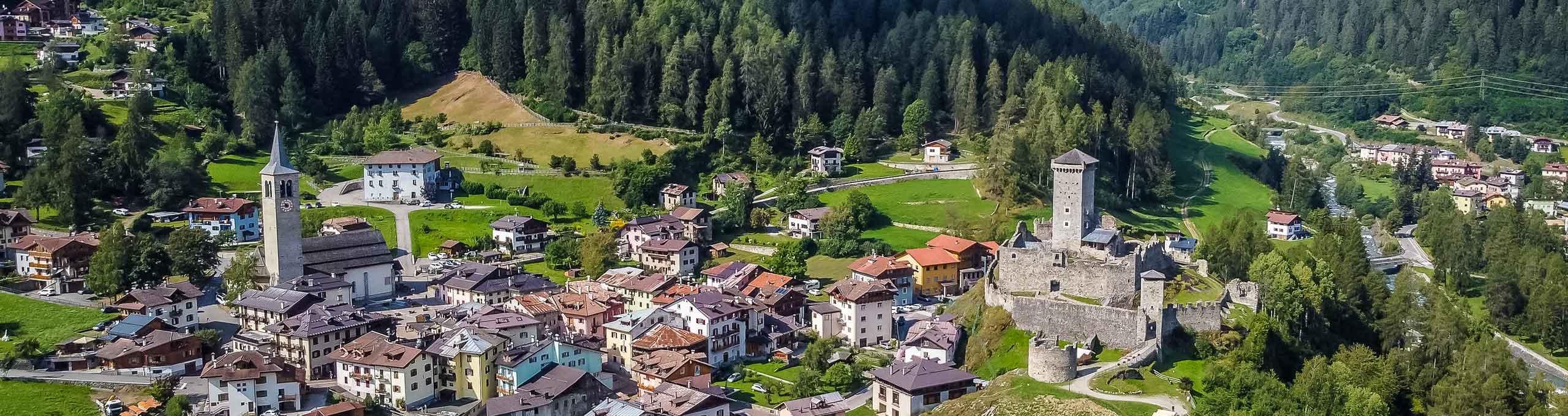 Vista aerea del villaggio di Ossana, sulla destra il Castello di San Michele
